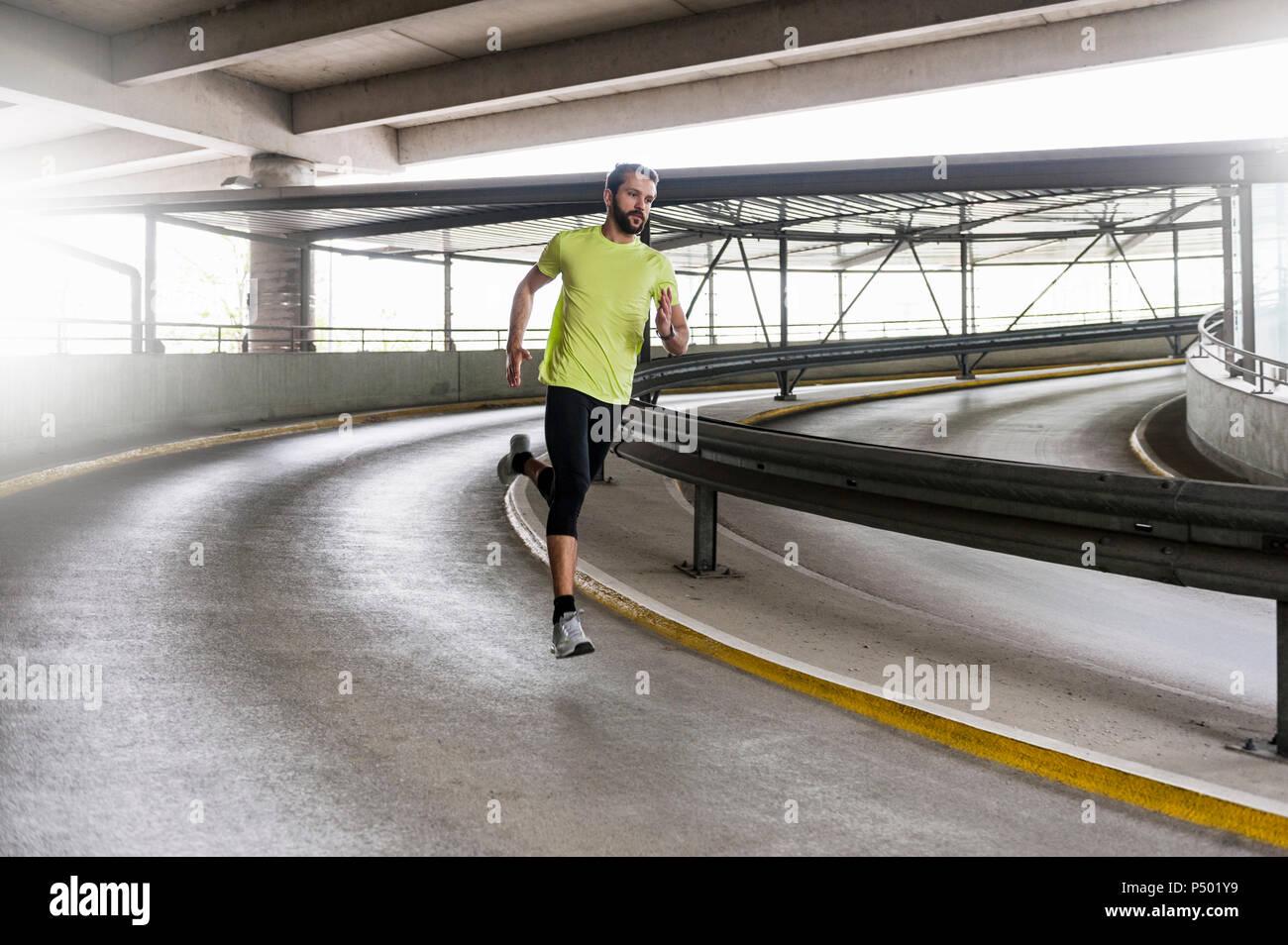 Homme qui court dans un garage de stationnement dans un virage Photo Stock