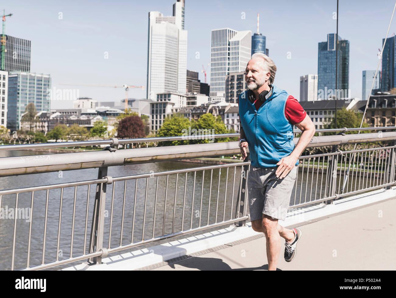Smiling mature man with headphones tournant sur le pont dans la ville Photo Stock