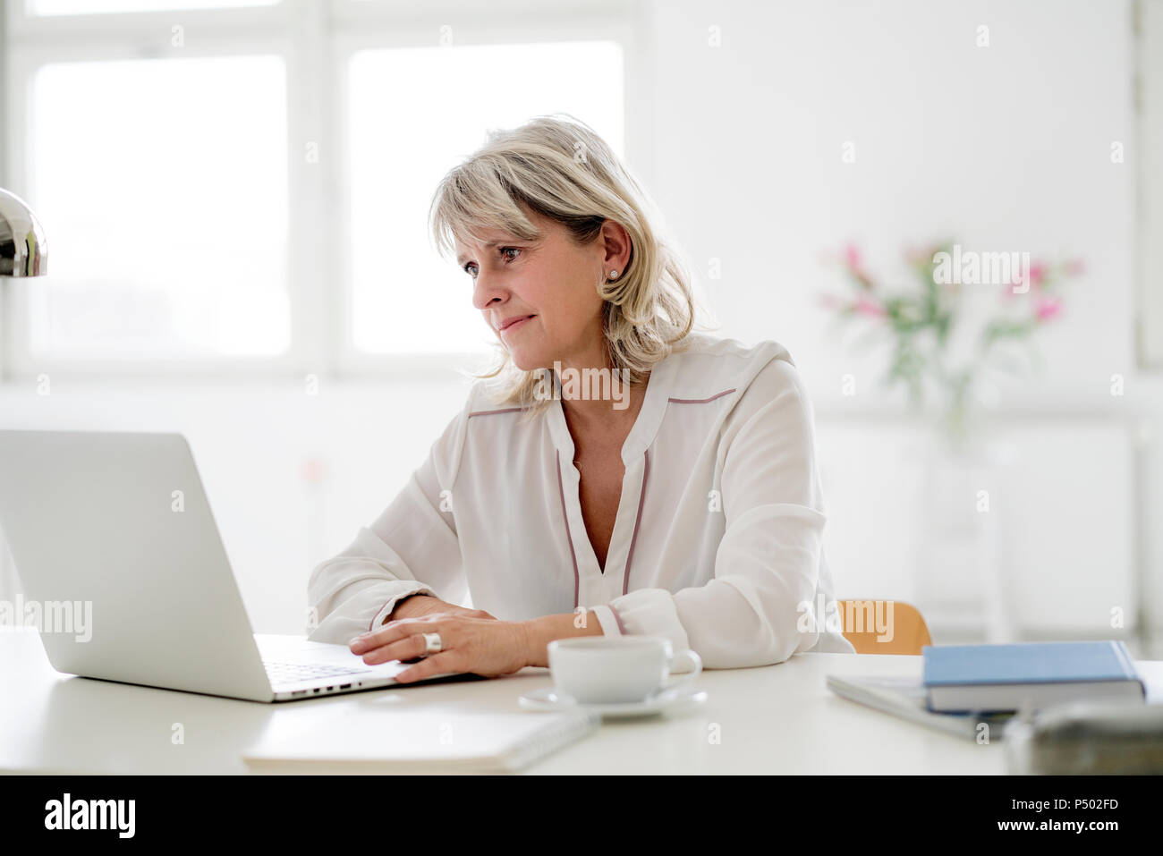 Smiling mature woman working on laptop at desk Photo Stock