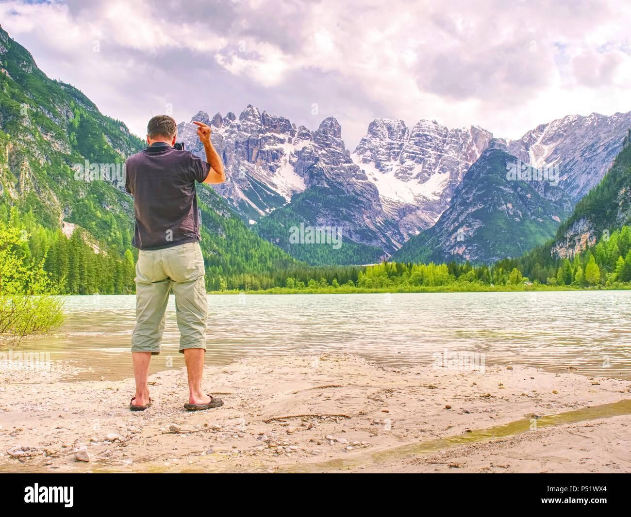 Homme randonneur est taking photo du navire au rivage de lac de montagne. Silhouette à la pêche pédalo au lac de l'autre. Photo Stock