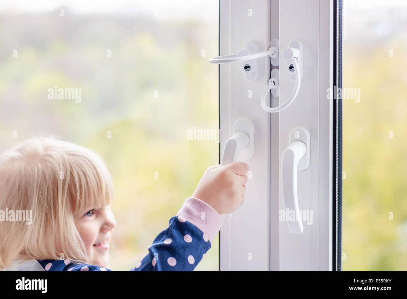 Cute Little Girl Essayant Douvrir La Fenêtre Dans Lappartement à