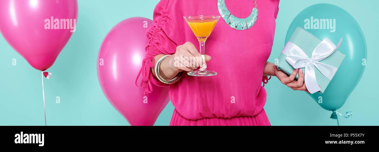 Superbe jeune femme dans party outfit tenue cadeau d'anniversaire et plus isolées, cocktail bleu pastel arrière-plan coloré. Bannière de fête d'anniversaire. Banque D'Images