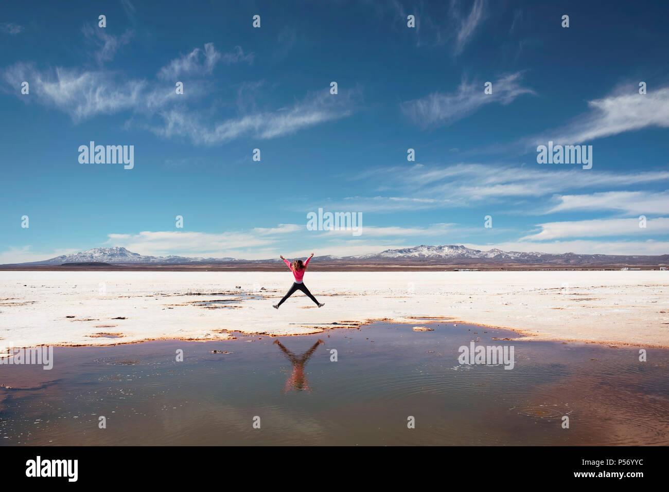 Heureux de sauter sur le côté d'une flaque d'eau salée naturelle au Salar de Uyuni, Bolivie. Photo Stock