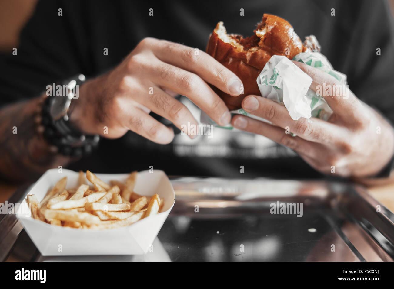 Jeune homme barbu eating hamburger et frites de près. Photo Stock