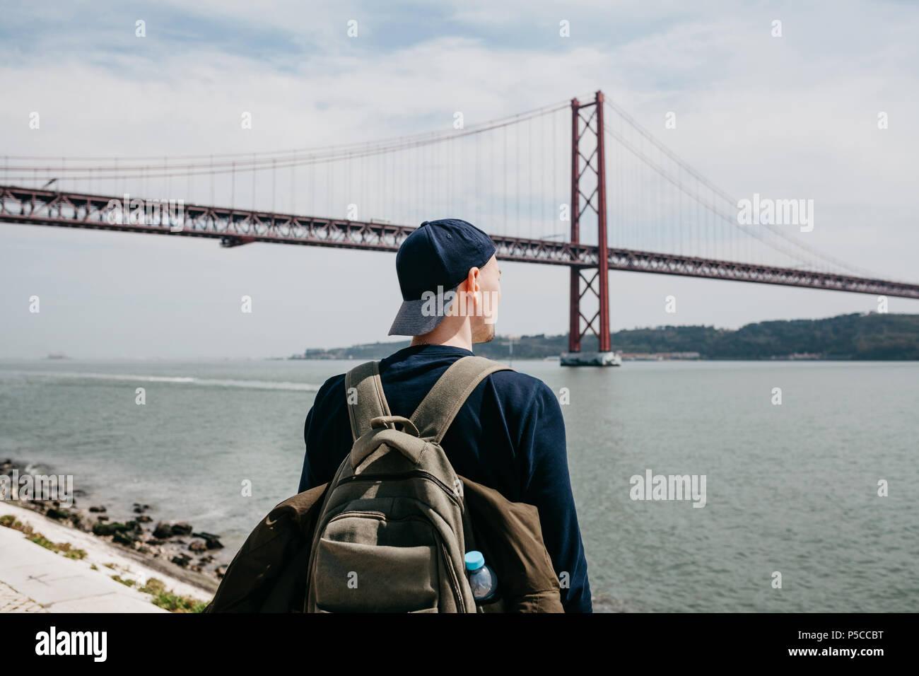 Un jeune voyageur ou touriste avec un sac à dos sur le bord de l'eau à Lisbonne au Portugal, à côté de la pont du 25 avril Photo Stock