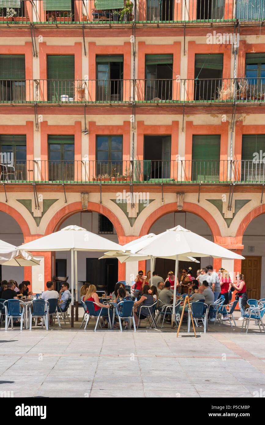 Cordoba bar café, les touristes se détendre lors d'une terrasse de café dans le 17e siècle, la Plaza de la Corredera à Cordoue par un après-midi d'été, Andalousie, espagne. Photo Stock