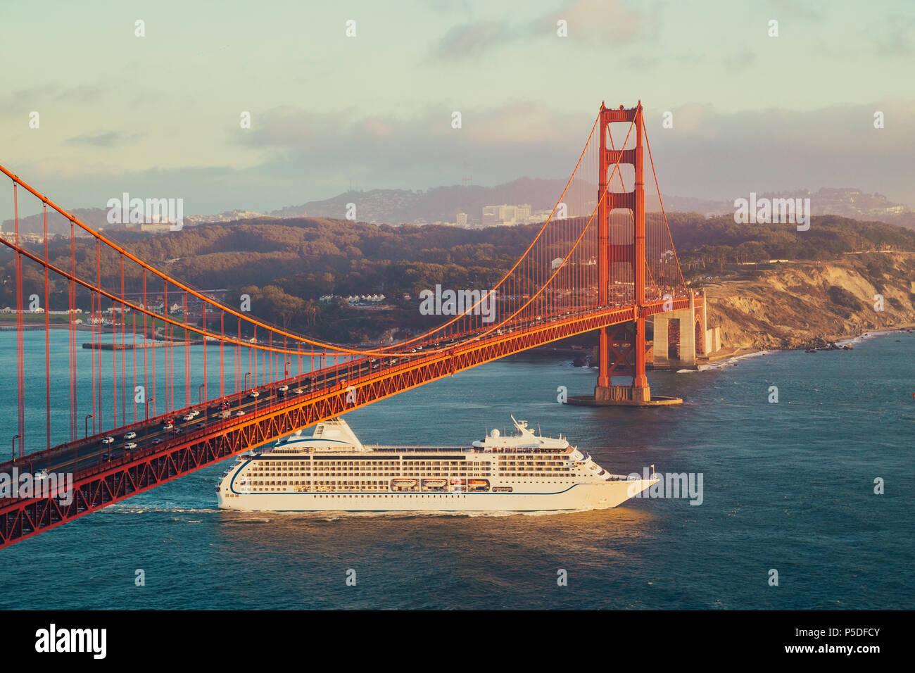 Belle vue panoramique de navire de croisière passant célèbre Golden Gate Bridge avec la skyline de San Francisco en arrière-plan dans la belle golden eveni Banque D'Images
