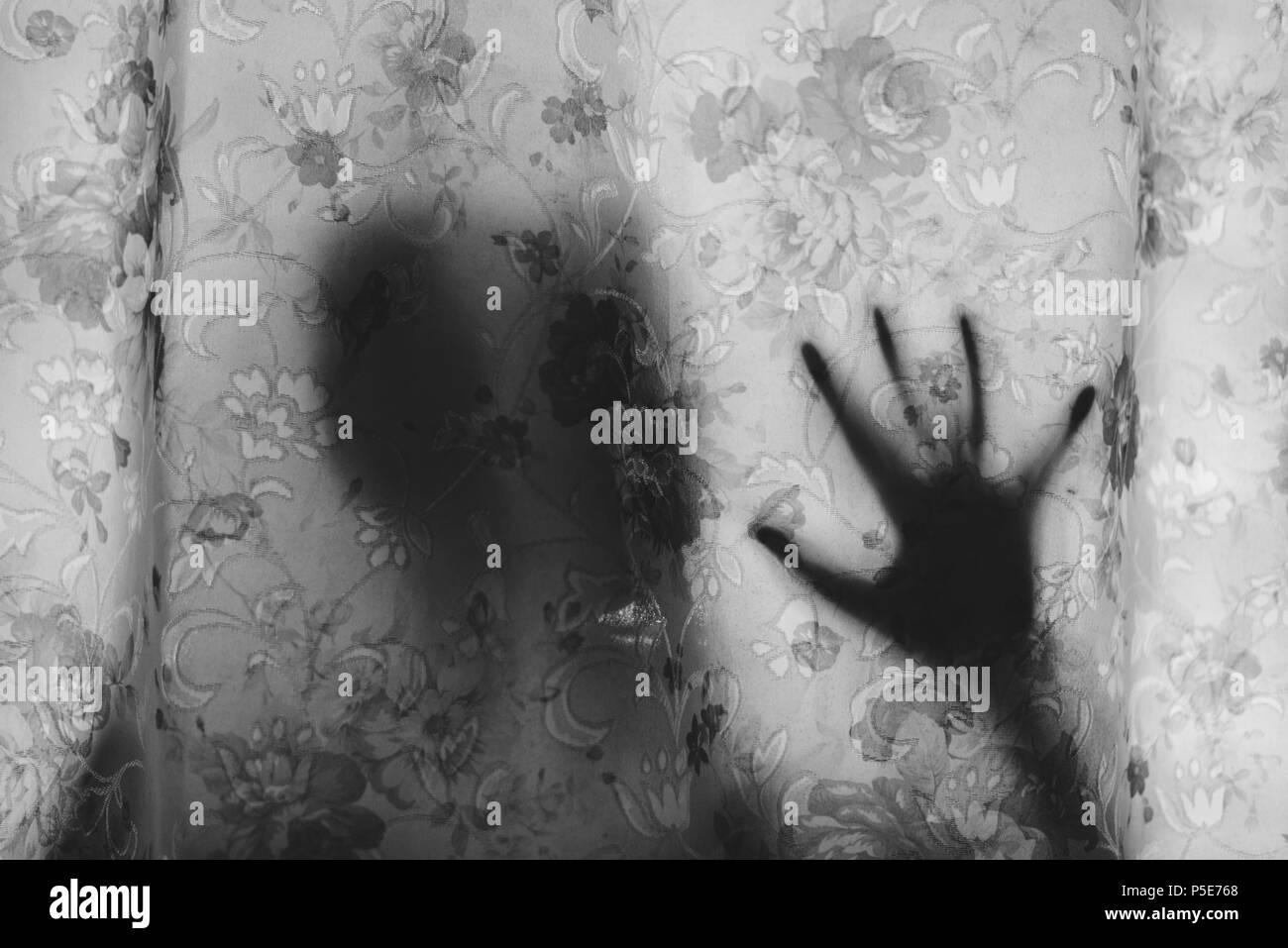 Image en noir et blanc de la mystérieuse ombre derrière un rideau. la peur, mystère, effrayant, glauque et concept paranormal Photo Stock