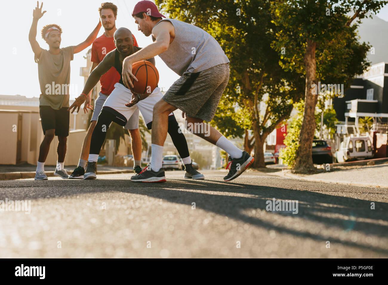 Les hommes jouant au basket-ball jeu sur une journée ensoleillée sur une rue vide. Les hommes pratiquant le basket-ball ses dribbles sur rue. Banque D'Images