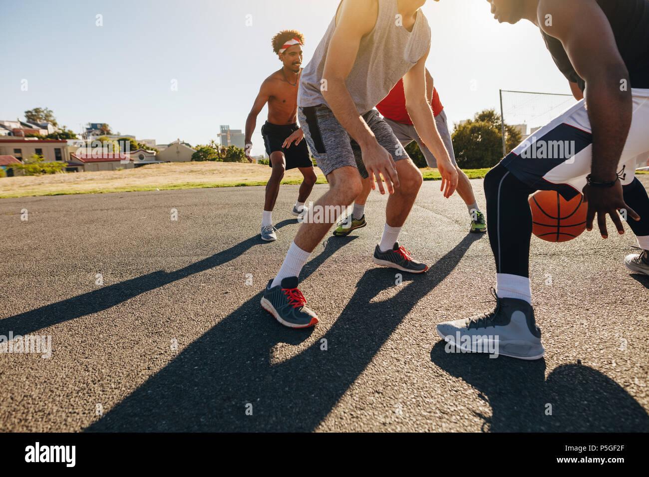 Les hommes jouant au basket-ball jeu sur une journée ensoleillée. Les hommes exerçant des compétences de basket-ball dans l'aire de jeu. Banque D'Images