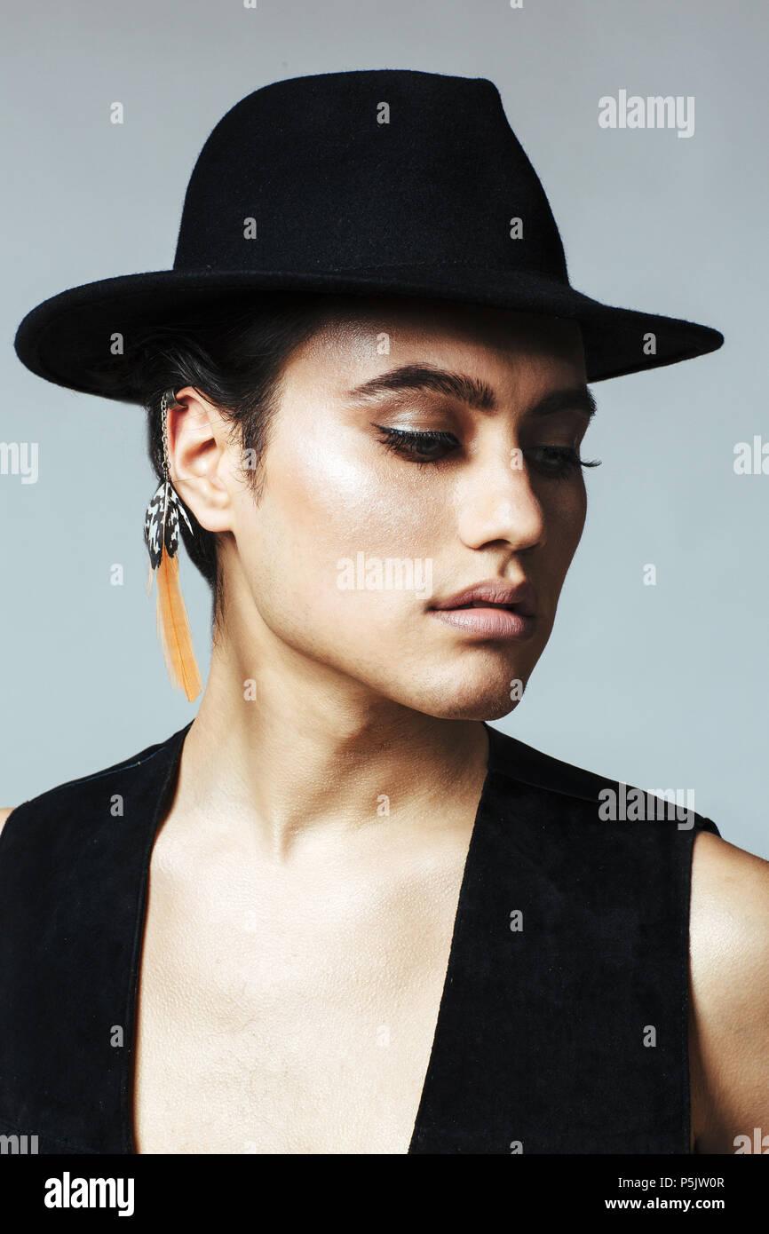 9333ddfbae72c Portrait vertical d'un jeune homme avec chapeau noir, ombre à paupières et  earring