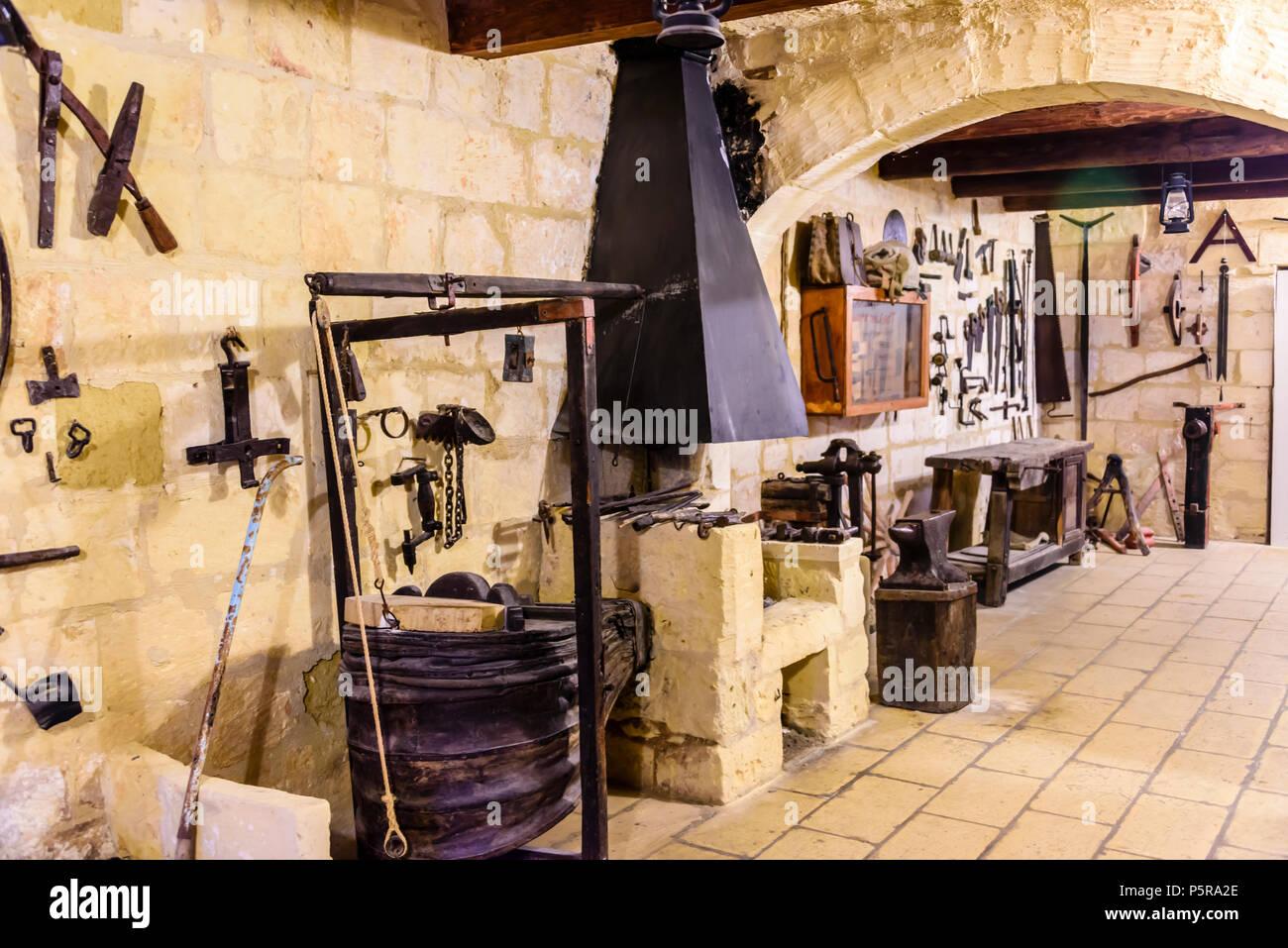 Vieux outils traditionnels accroché sur un mur dans un atelier de travail du bois et du métal. Banque D'Images