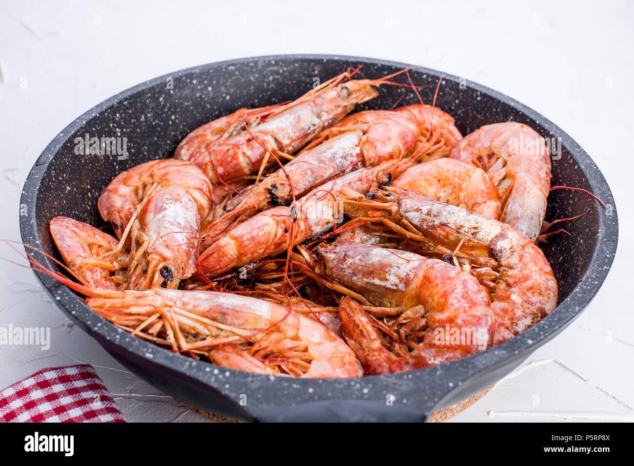 Grosses crevettes frits dans une poêle. Sur un tableau blanc. Le déjeuner de fruits de mer. Espace libre pour le texte. Copy space Photo Stock