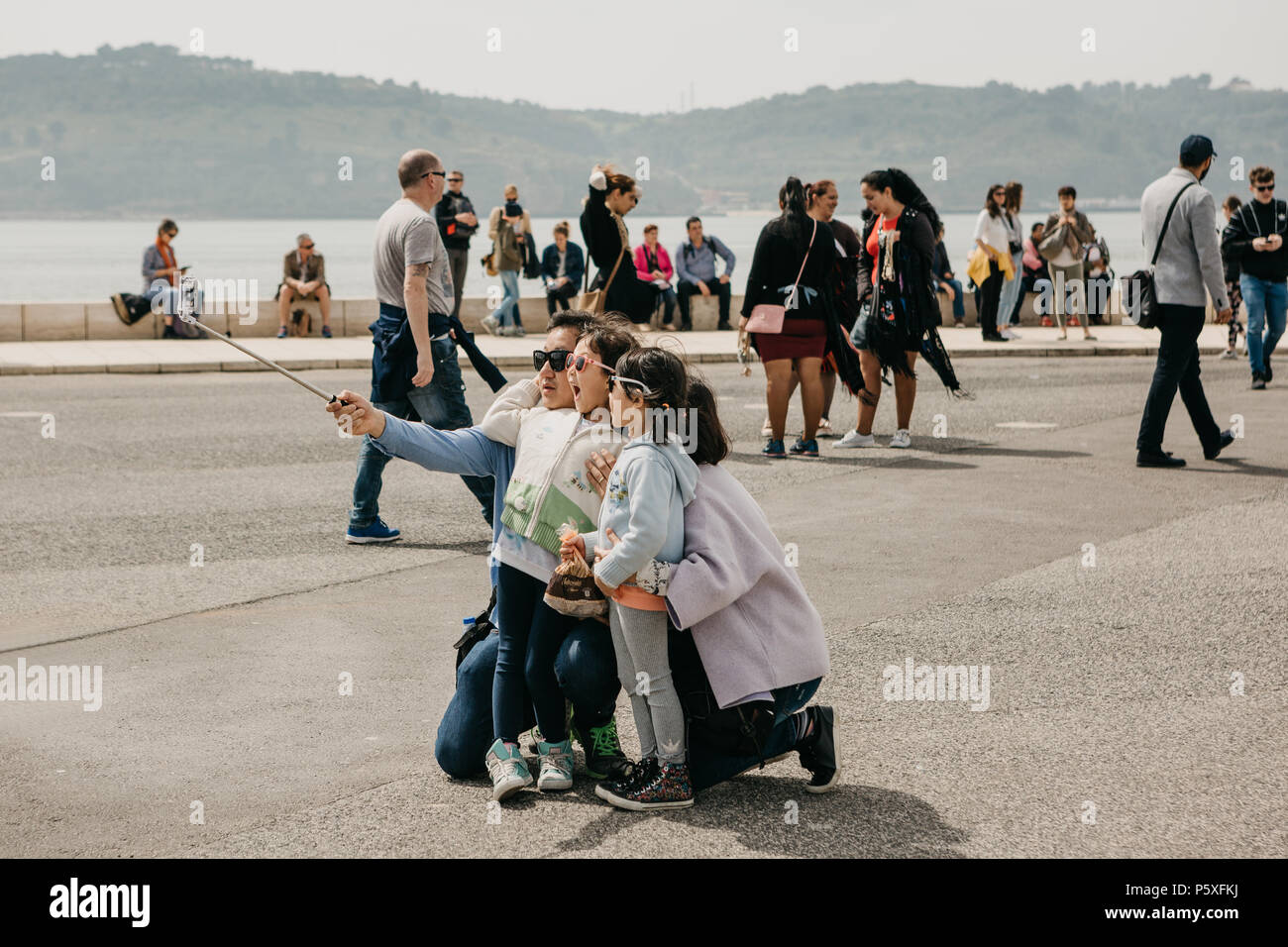Portugal, Lisbonne, 1 mai 2018: un jeune père de famille, la mère et les deux filles faire une selfies émotionnelle dans le secteur riverain de Belem. Les gens marchent autour de Photo Stock