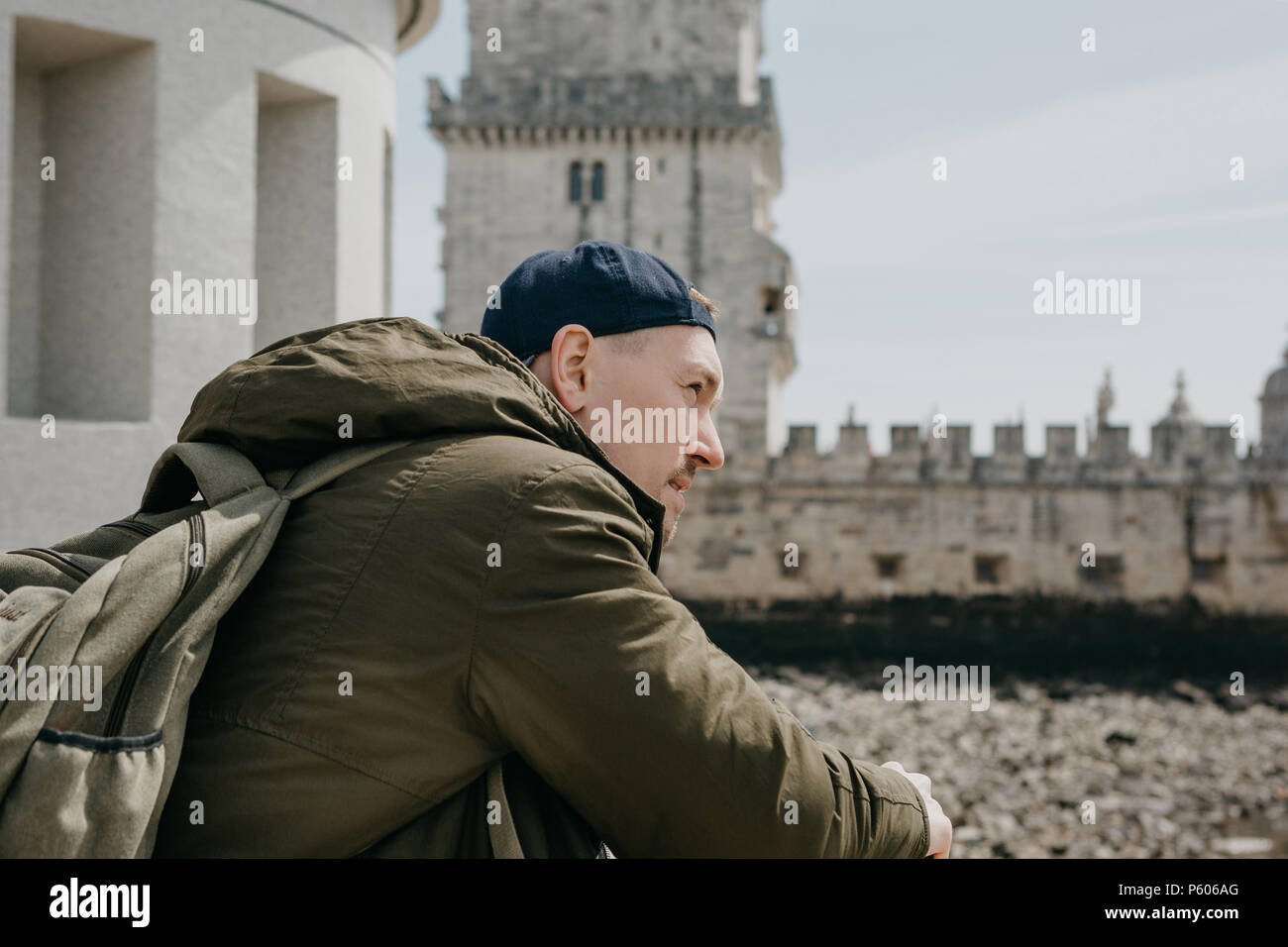 Portrait d'un jeune homme voyageur guy touristiques ou avec un sac à dos qui s'assied et regarde dans la distance à Lisbonne au Portugal. La Tour de Belém dans l'arrière-plan Photo Stock