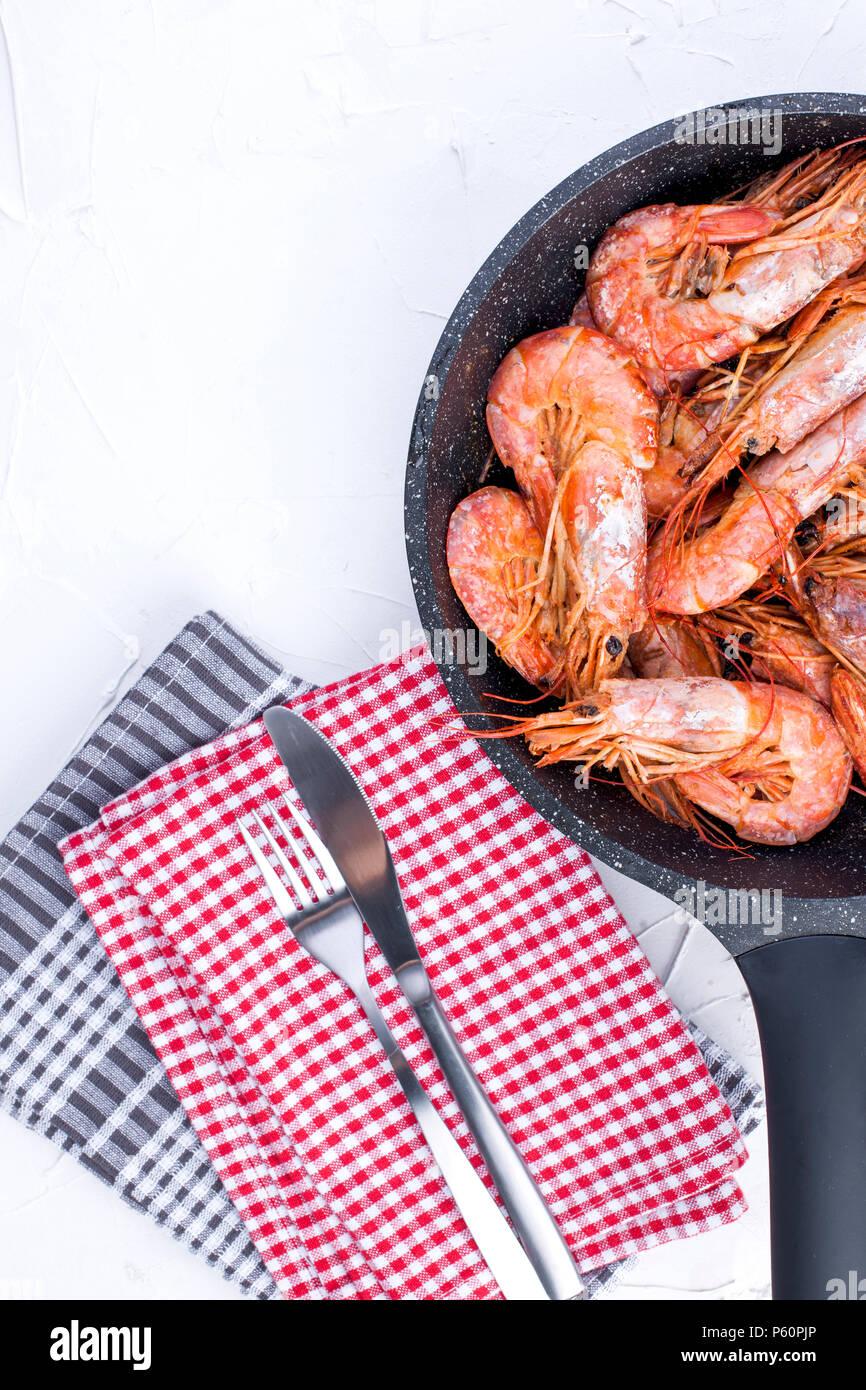 Grosses crevettes frits dans une poêle. Sur un tableau blanc et une table serviette. Le déjeuner de fruits de mer. Espace libre pour le texte. Copy space Banque D'Images