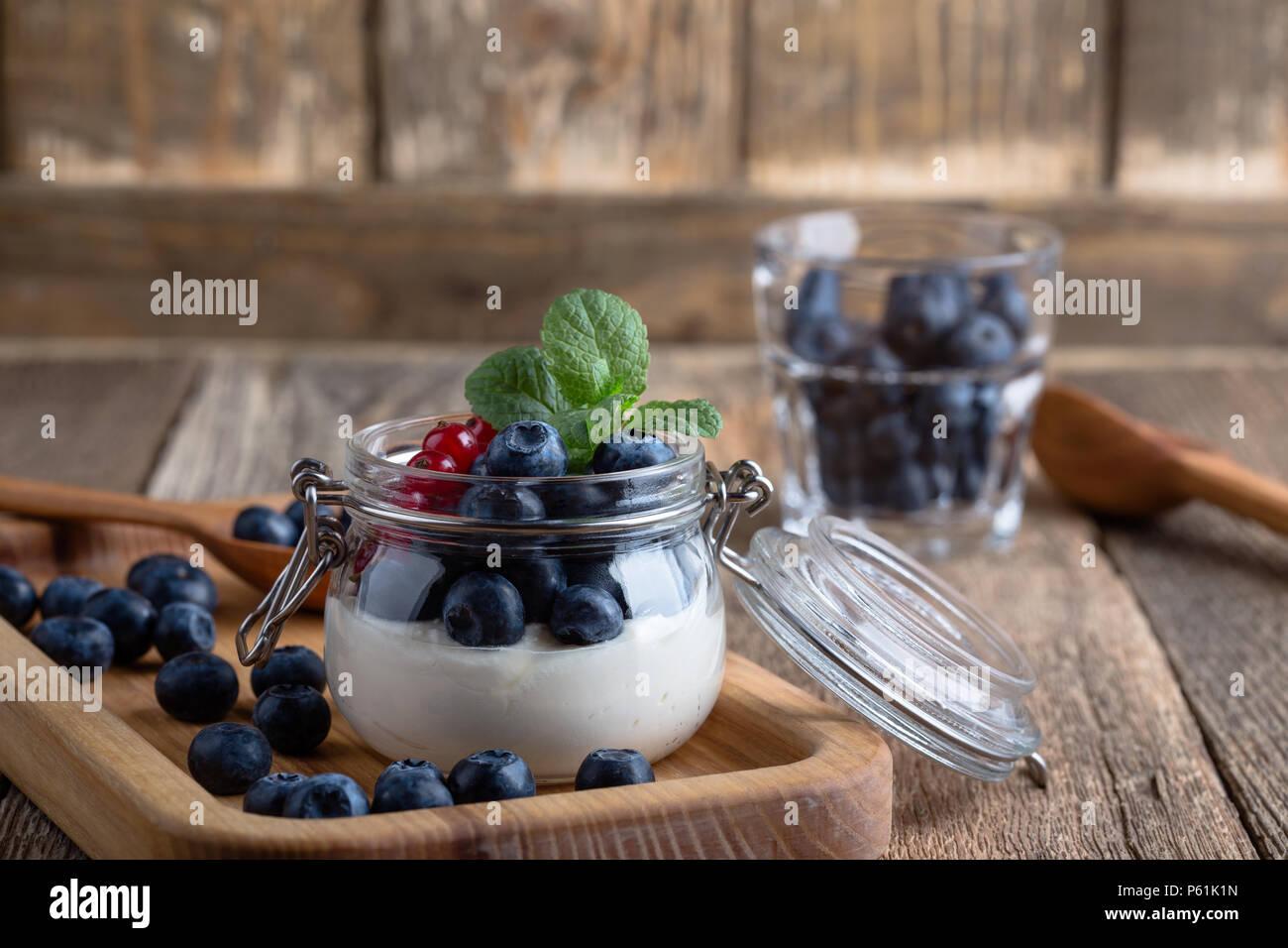 Les parfaits crème Cheesecake aux myrtilles et petits fruits groseille rouge servi dans un pot, sans cuisson d'été délicieux dessert sur la table rustique en bois prêt à manger Photo Stock