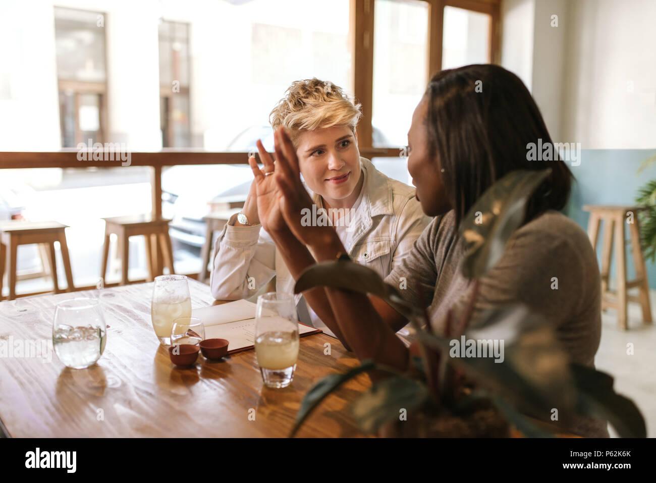 Serveur en parlant avec des clients assis à une table de bistro Banque D'Images
