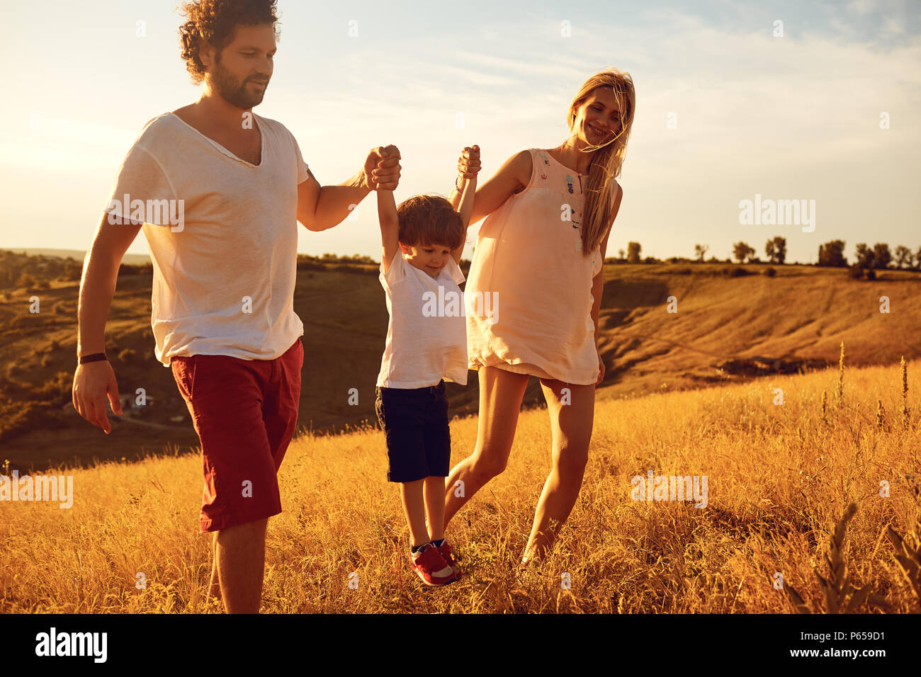 Happy Family having fun jouer au coucher du soleil. Photo Stock