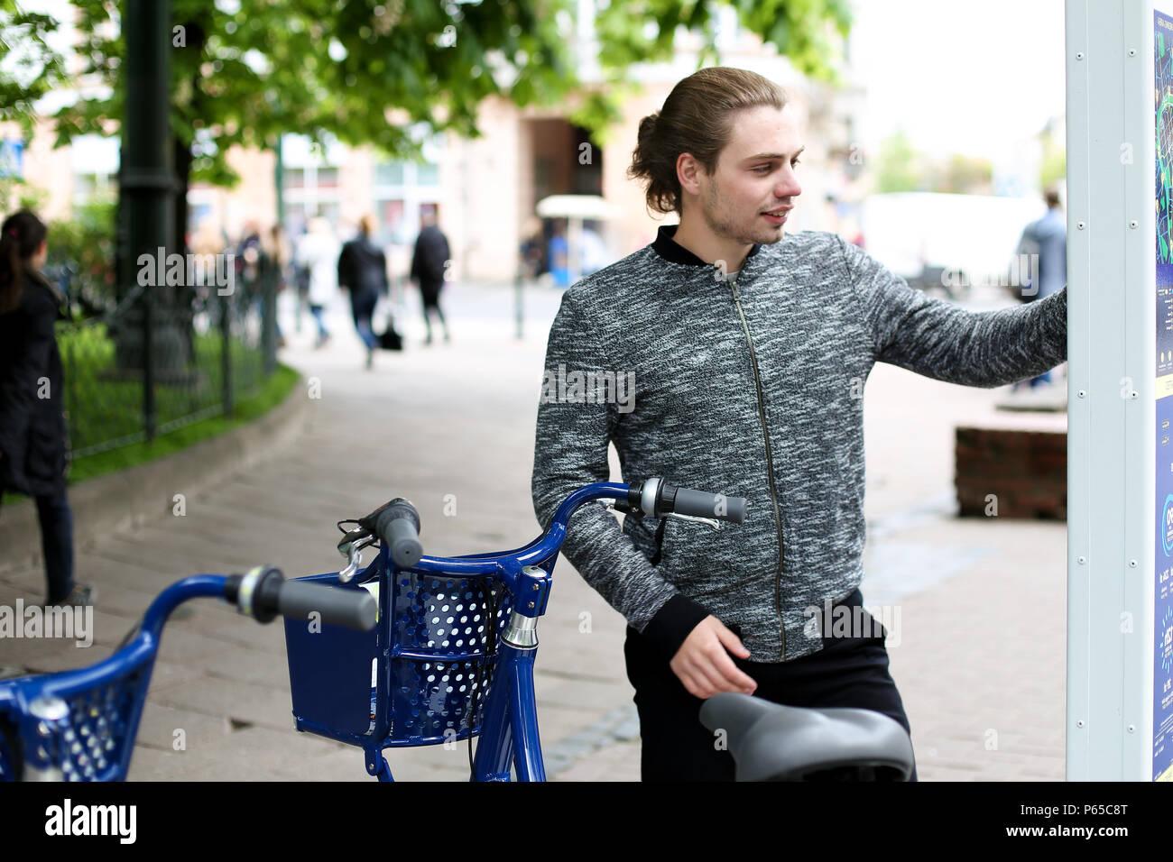 Jeune homme bleu embauche location avec la machine en ville. Photo Stock