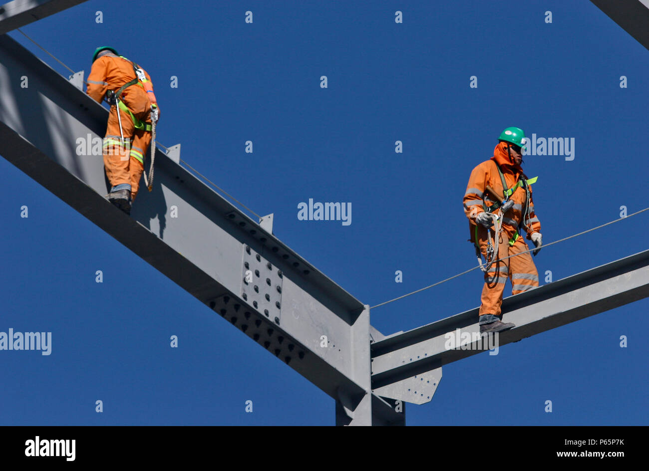 Les travailleurs de l'acier de marcher sur des poutres en acier avec fixation de sécurité Banque D'Images