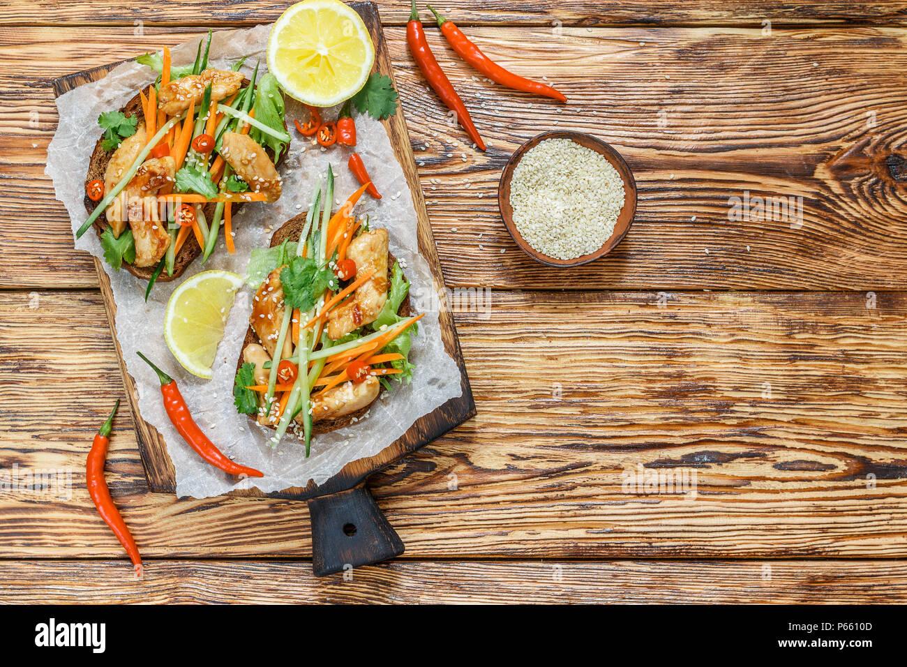 Sandwich asiatique avec du poulet frit et des légumes frais-carottes, concombre, piment, coriandre et sésame. Focus sélectif. Vue de dessus et copy space Photo Stock