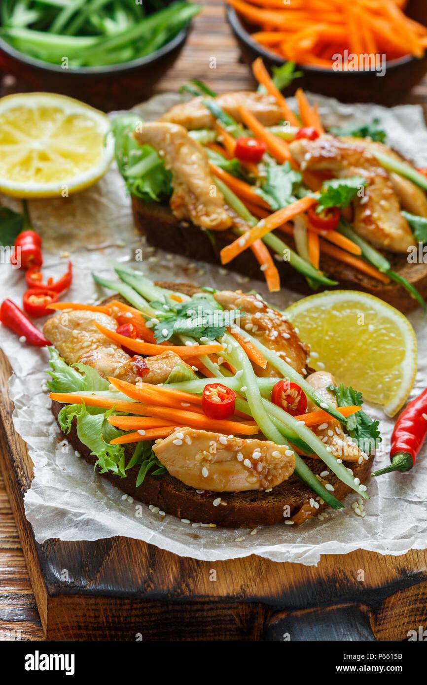 Sandwich asiatique avec du poulet frit et des légumes frais-carottes, concombre, piment, coriandre et sésame. Selective focus Photo Stock