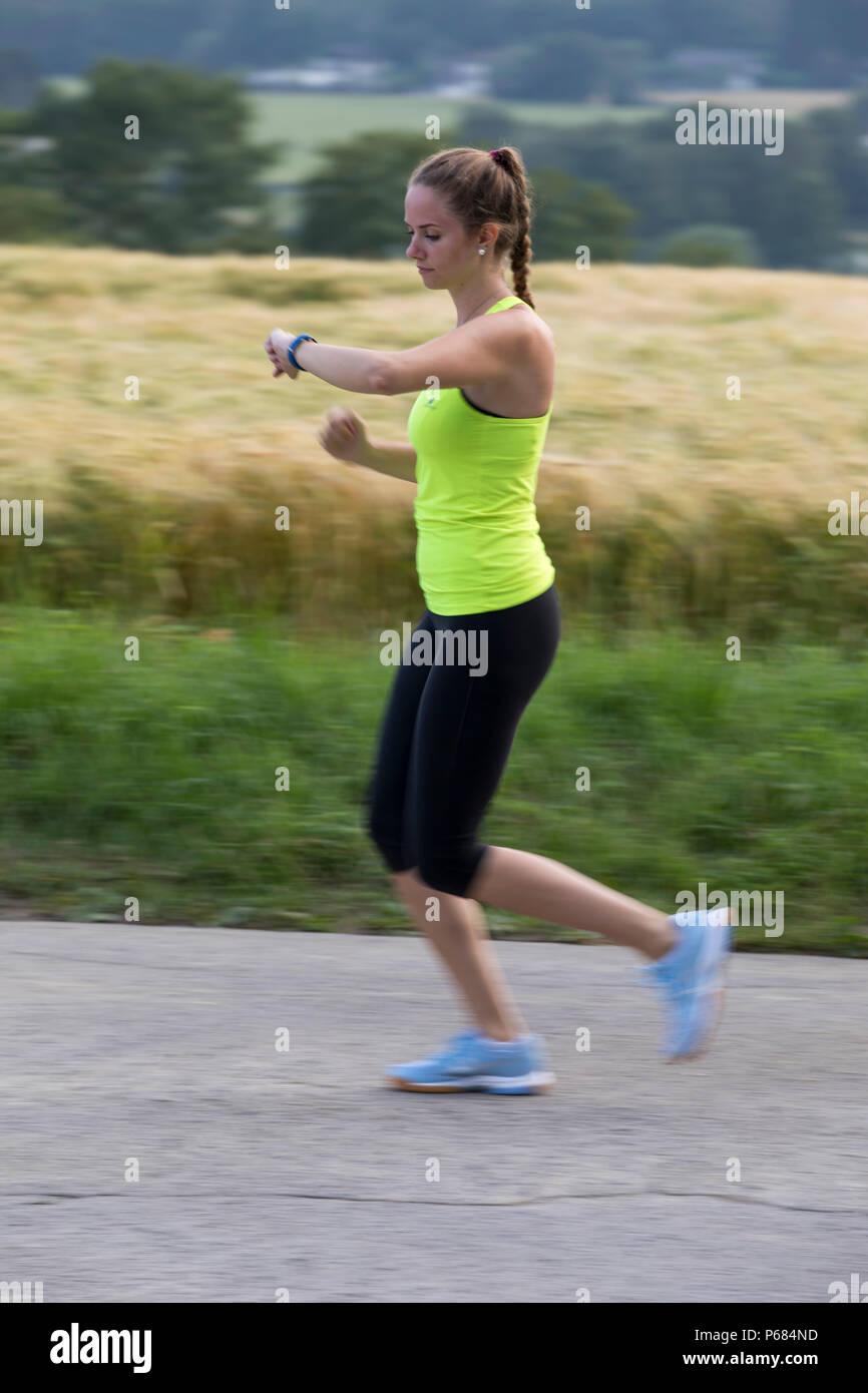 Young woman Jogging, course, contrôler ses paramètres vitaux dans une montre sport, fitness tracker, fréquence cardiaque, nombre de pas, distance, temps, calories brûler Photo Stock