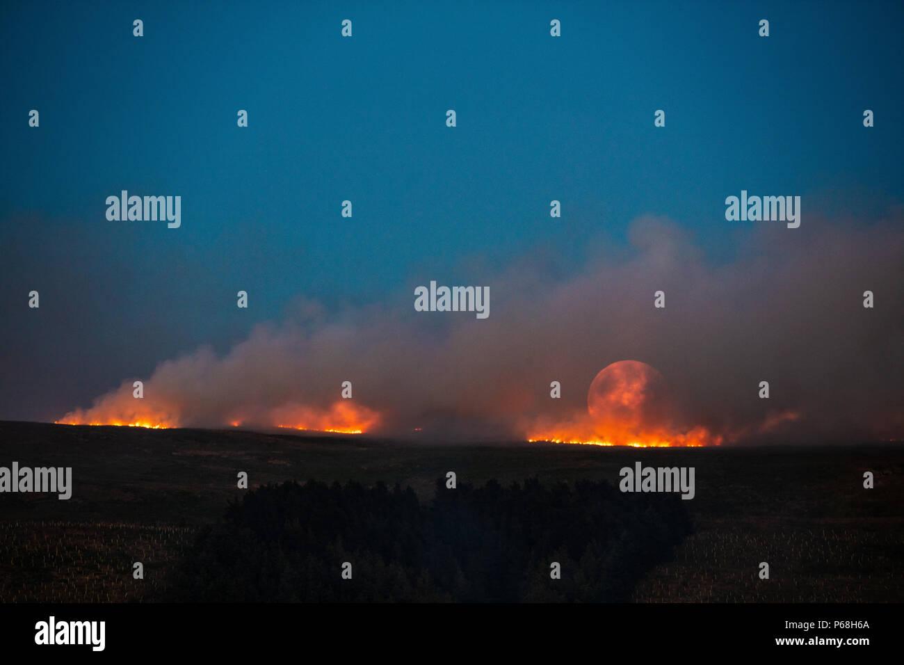 La colline d'hiver, le Grand Manchester, UK. 28 Jun, 2018. La lune se lève sur un feu d'herbe sur les terrains marécageux de la colline d'hiver, près de Bolton dans le Grand Manchester. Crédit: Jason Smalley Photography/Alamy Live News Banque D'Images