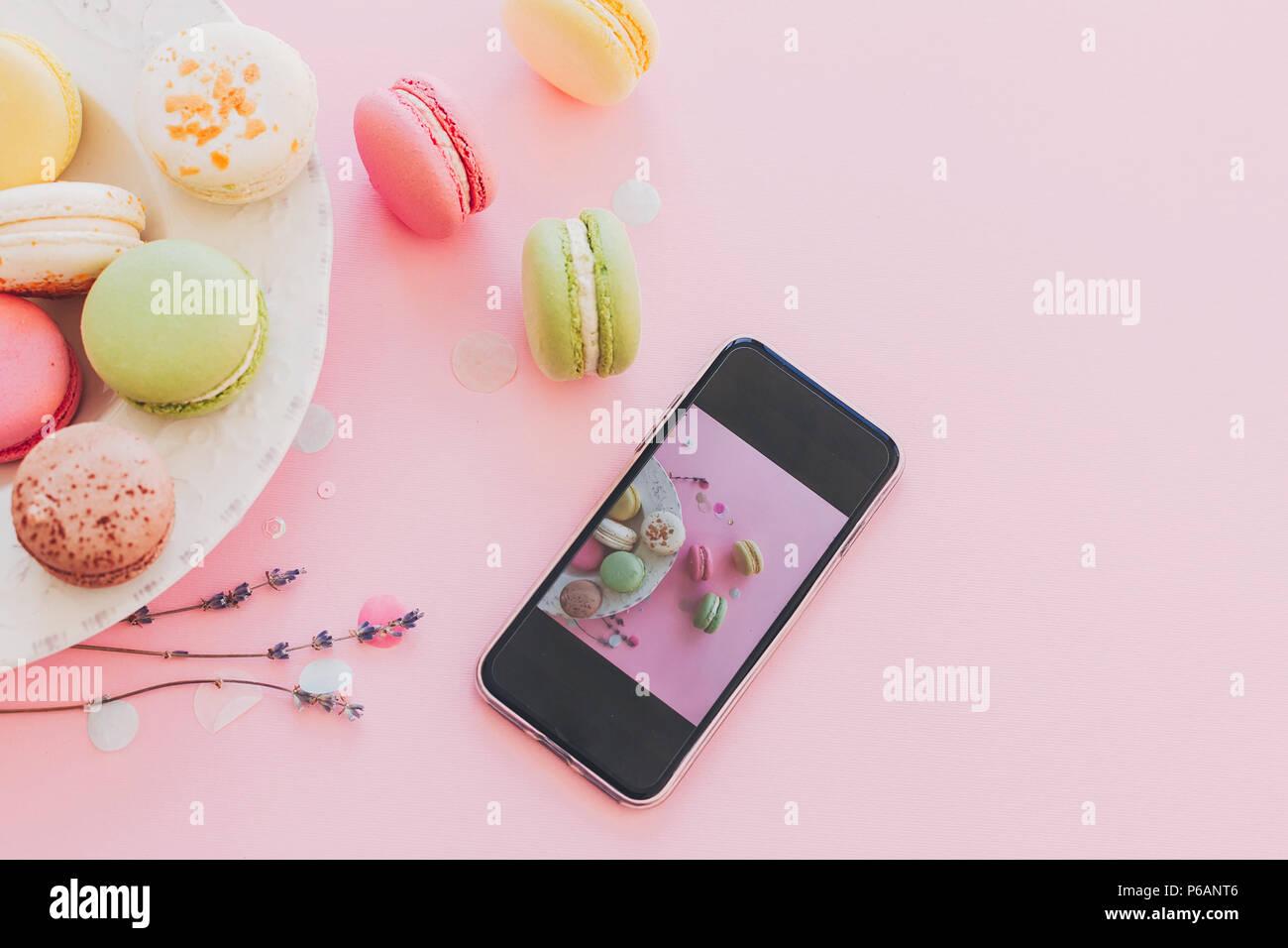 La photographie alimentaire moderne concept. téléphone avec photo de macarons colorés de style vintage très tendance en plaque sur papier rose avec lavande. espace pour texte. je Photo Stock