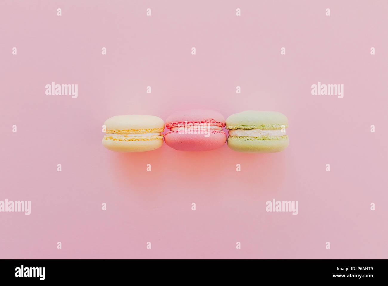 Macarons colorés de style branché sur du papier rose, télévision lay. espace pour texte. Une cuisine moderne concept photographie. délicieux rose, jaune, vert macarons, yummy Photo Stock