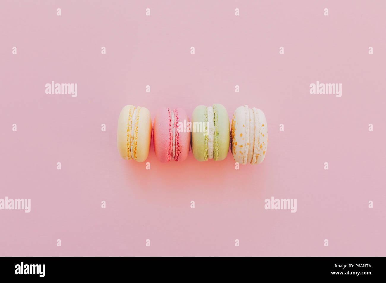 Macarons colorés de style branché sur du papier rose, télévision lay. espace pour texte. Une cuisine moderne concept photographie. délicieux rose, jaune, vert, blanc macarons Photo Stock