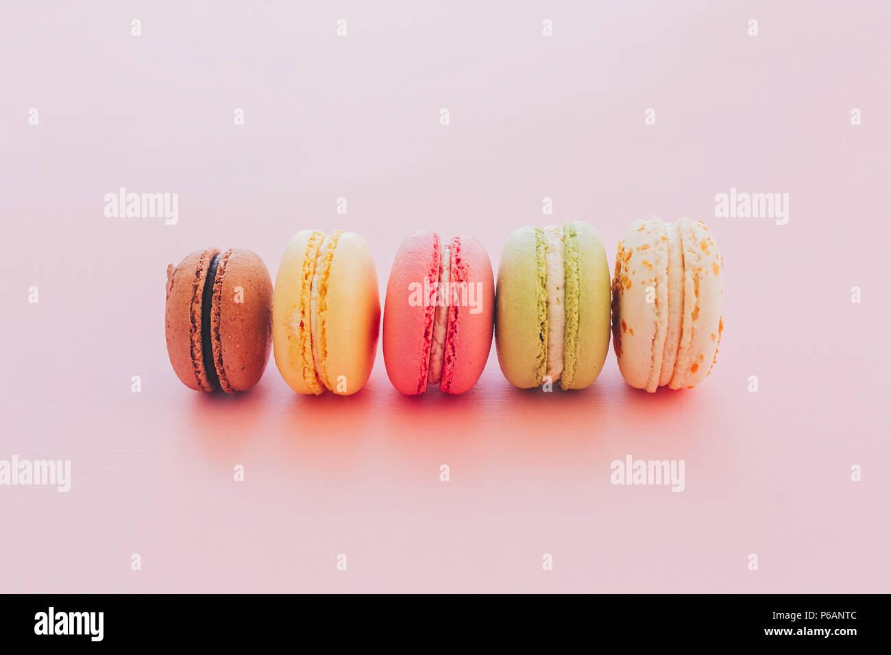 Macarons colorés de style branché sur du papier rose. Un espace réservé au texte.délicieux rose, jaune, vert, blanc, marron macarons. yummy. arrière-plan de l'alimentation moderne photographe Photo Stock