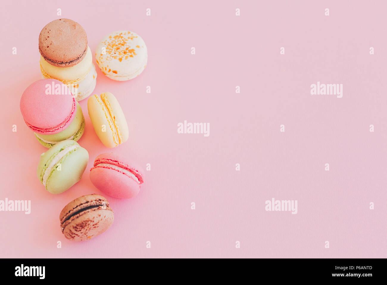 Macarons colorés de style branché sur du papier rose, télévision lay. espace pour texte. Une cuisine moderne concept photographie. délicieux rose, jaune, vert, blanc, marron ma Photo Stock