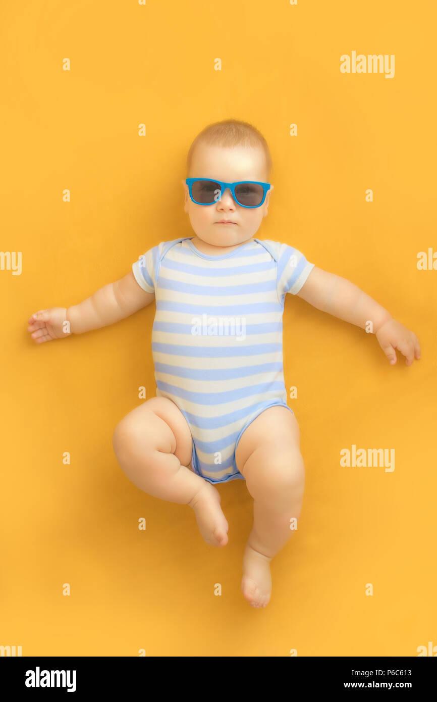d14579660fcf52 Mignon bébé avec des lunettes de soleil allongé sur une robe orange portant  Costume marin bébé