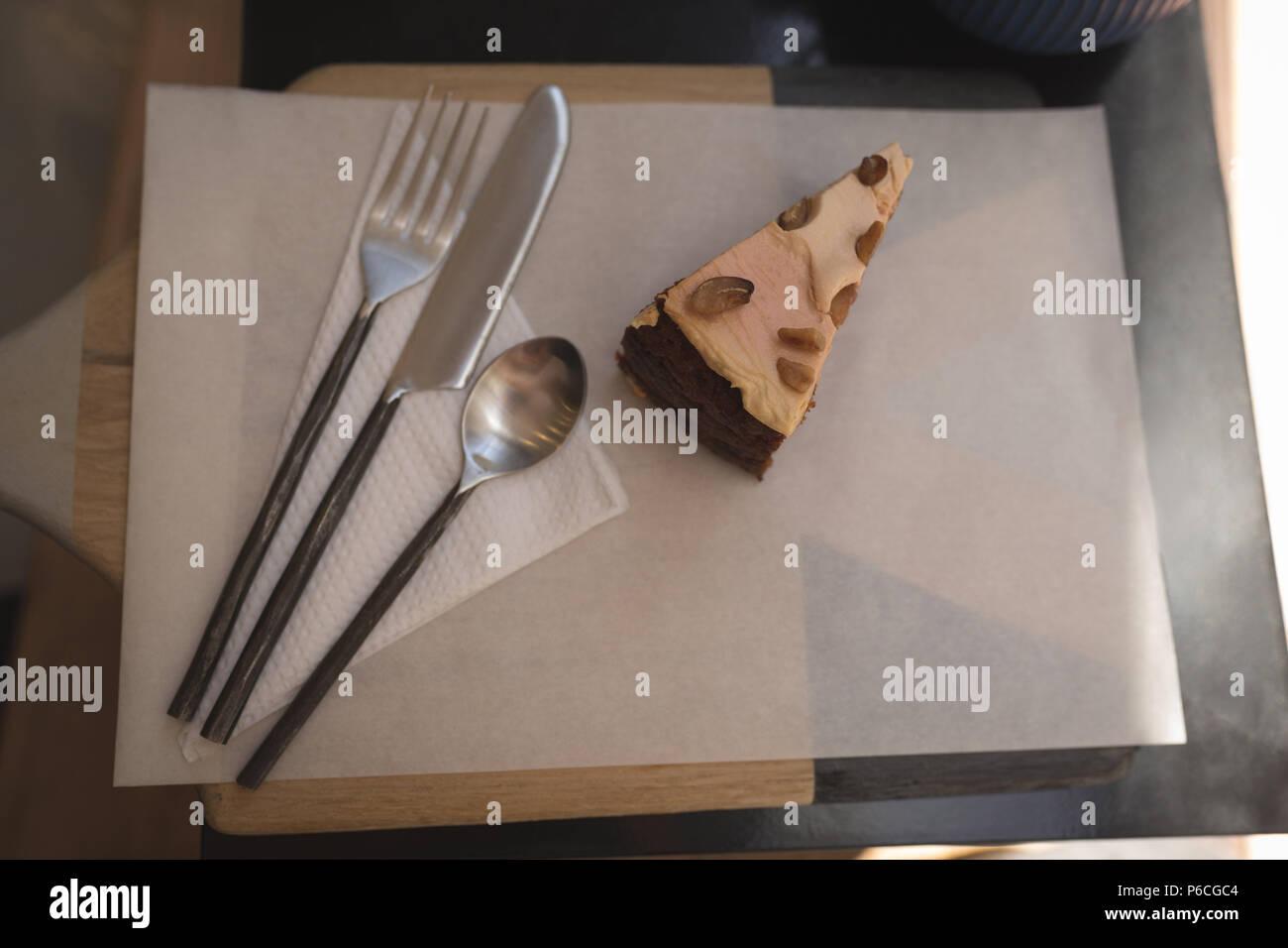 Gâteau de pâte avec une cuillère, fourchette et couteau à beurre sur un papier ciré Banque D'Images