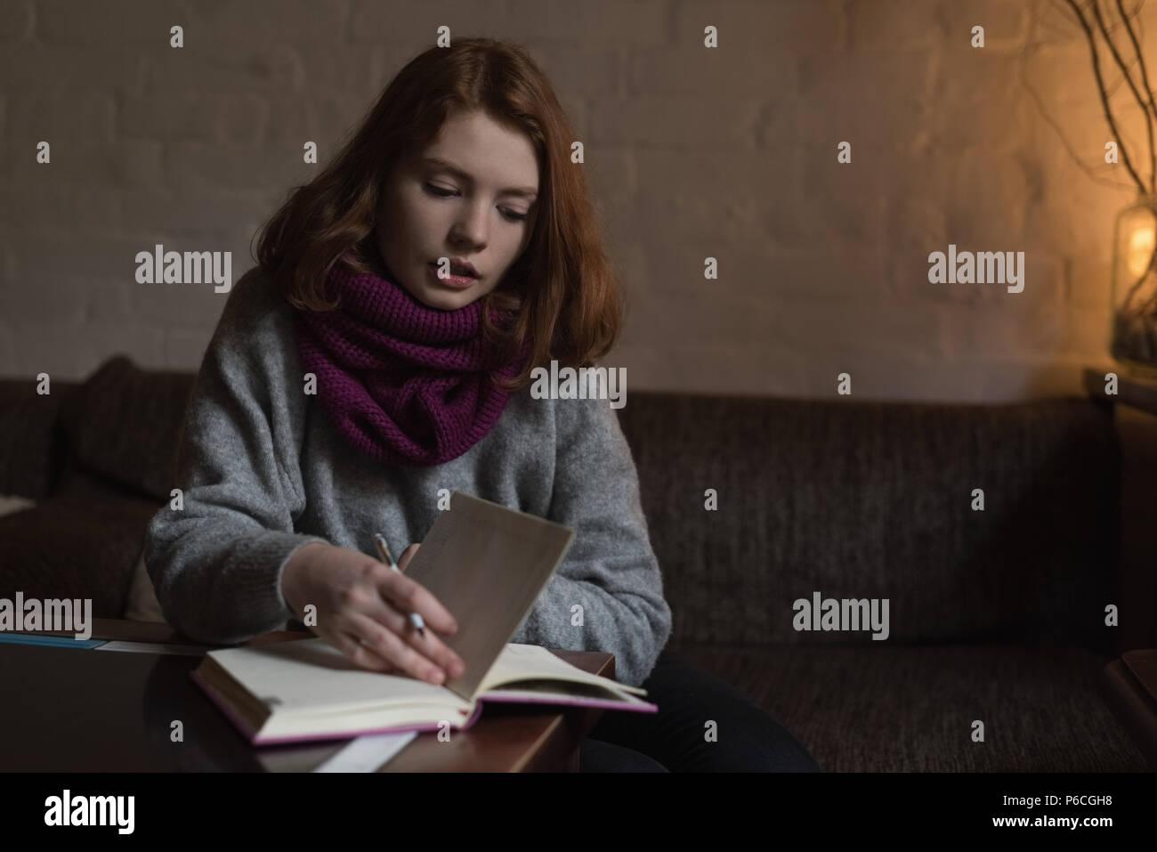 Femme écrit note sur l'agenda dans la salle de séjour Banque D'Images
