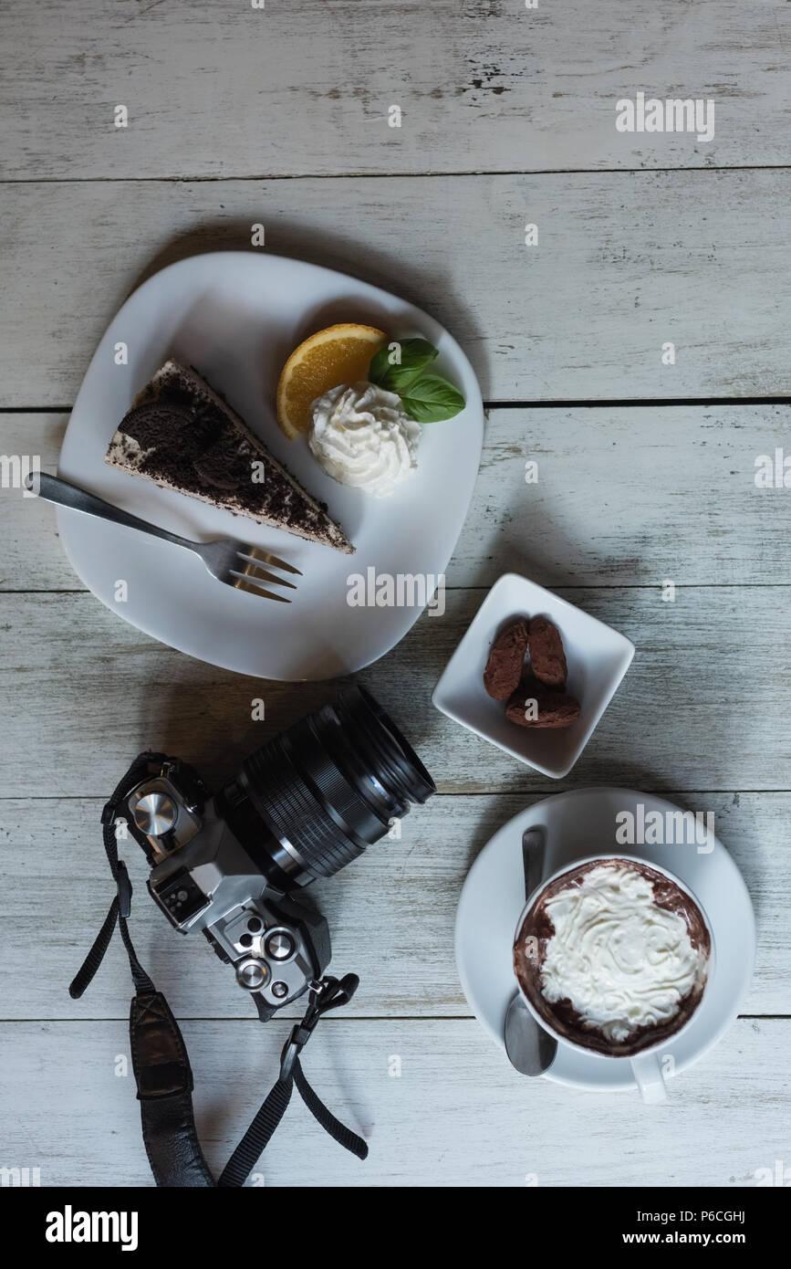 Appareil photo et délicieux de la nourriture sur table en bois Banque D'Images