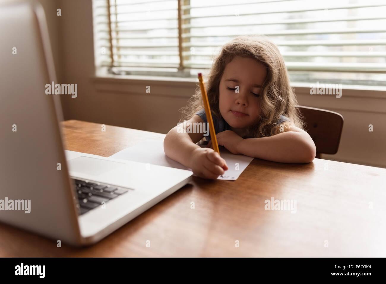 Girl écrit avec un crayon sur une feuille de papier. Banque D'Images
