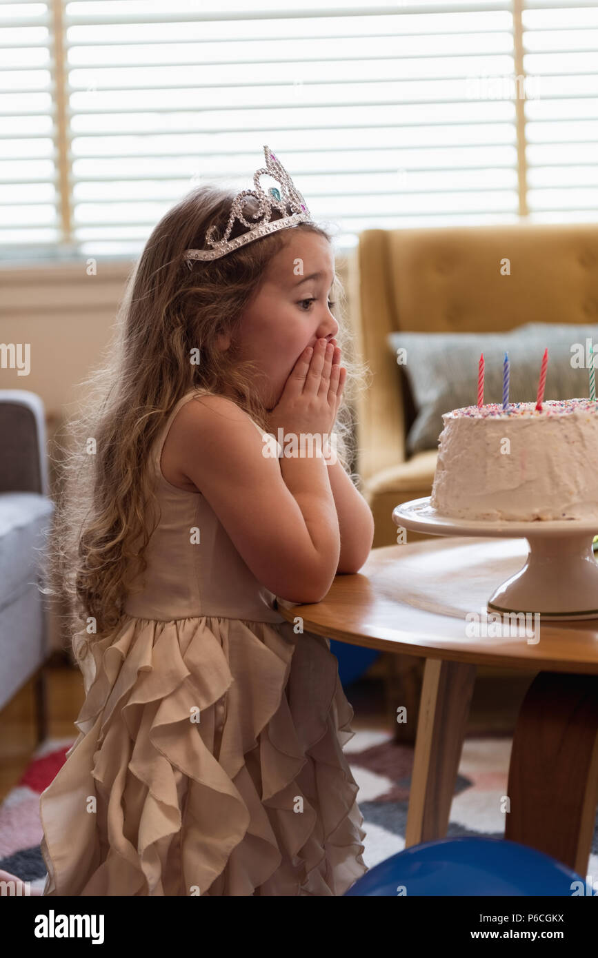 Surpris girl looking at her birthday cake Banque D'Images