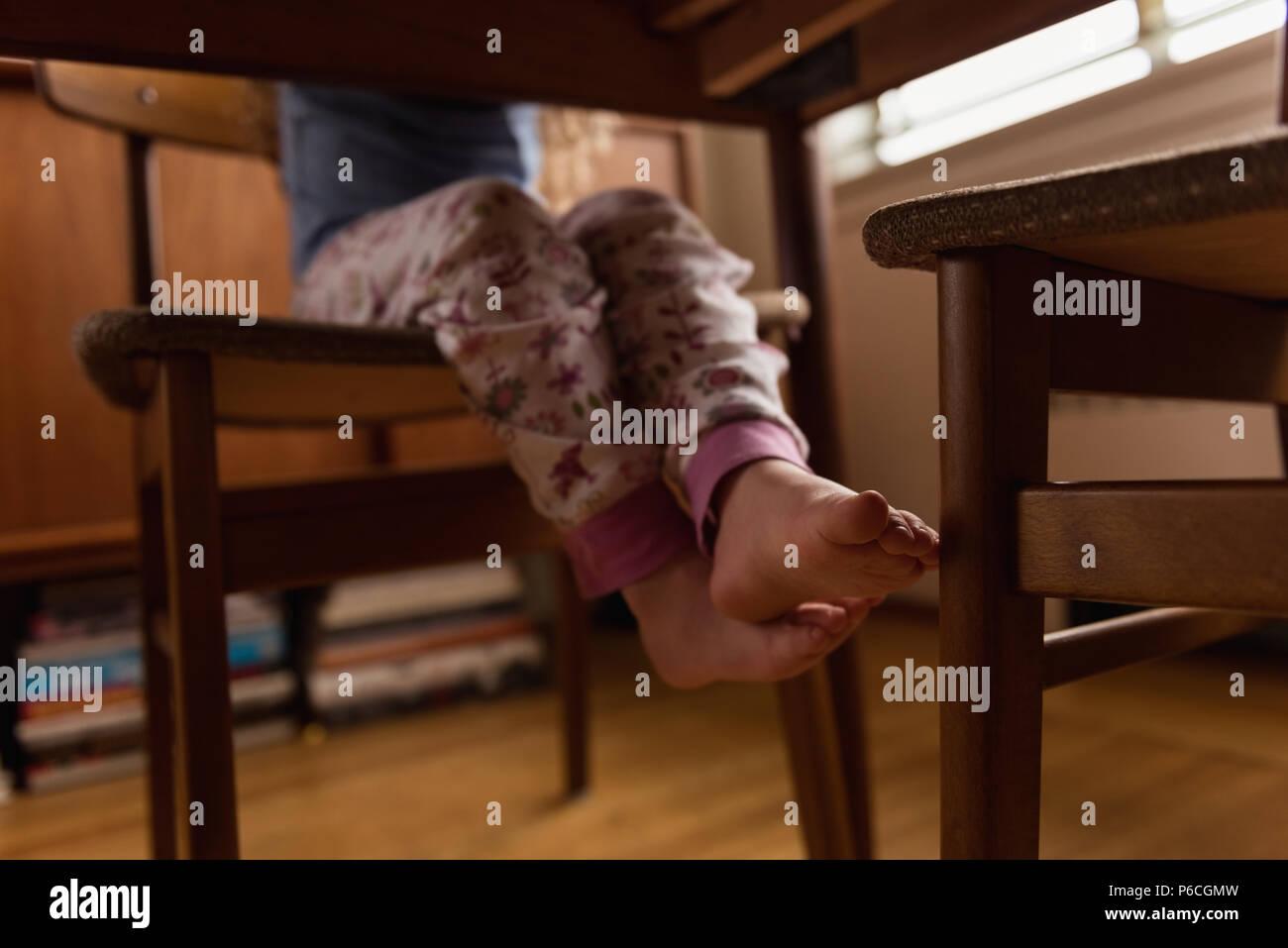Petite fille assise sur une chaise à la maison Banque D'Images