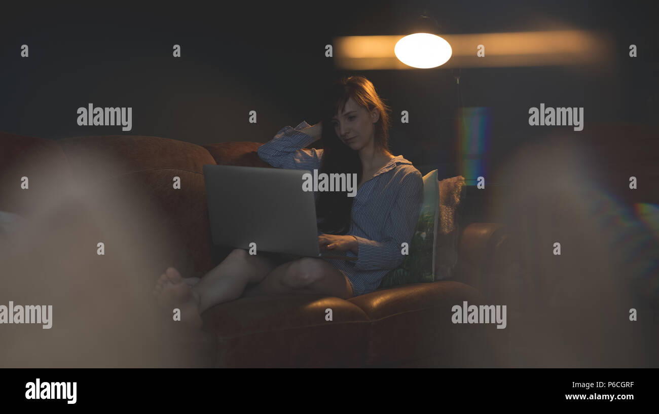 Woman on sofa in living room Banque D'Images
