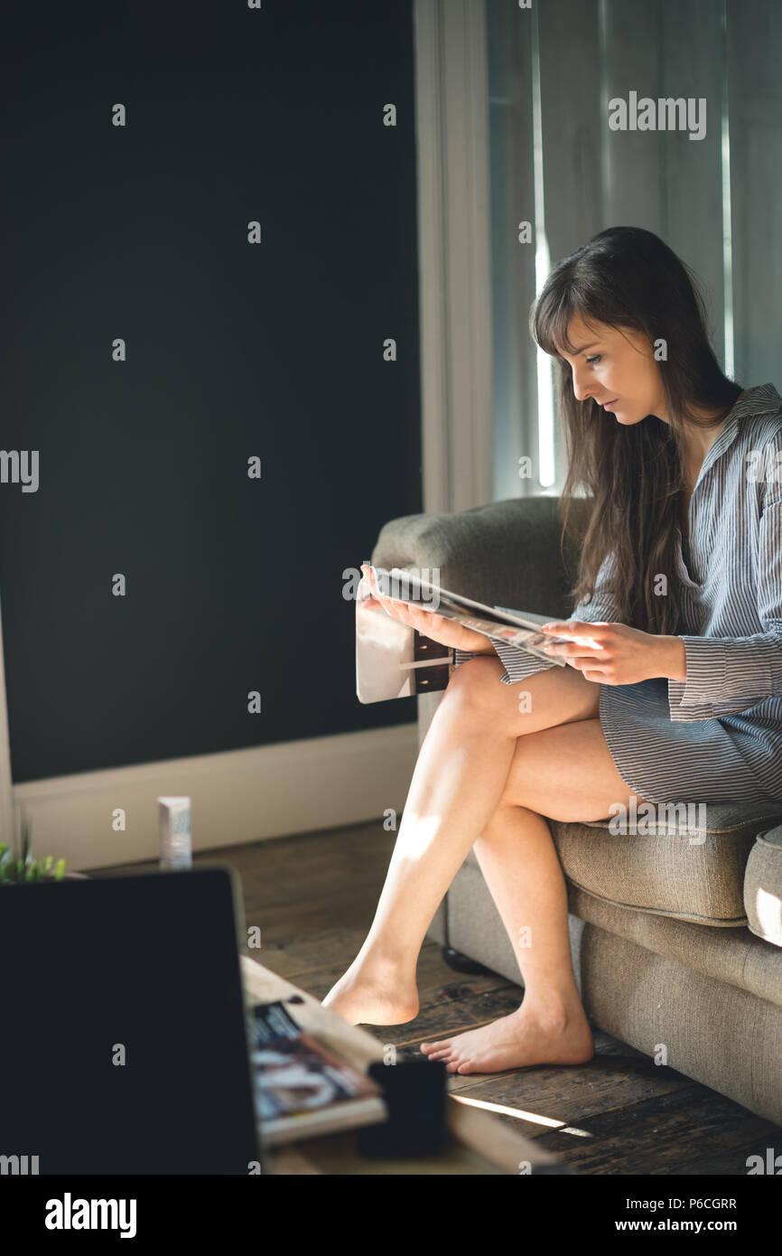 Woman Reading magazine dans la salle de séjour Banque D'Images