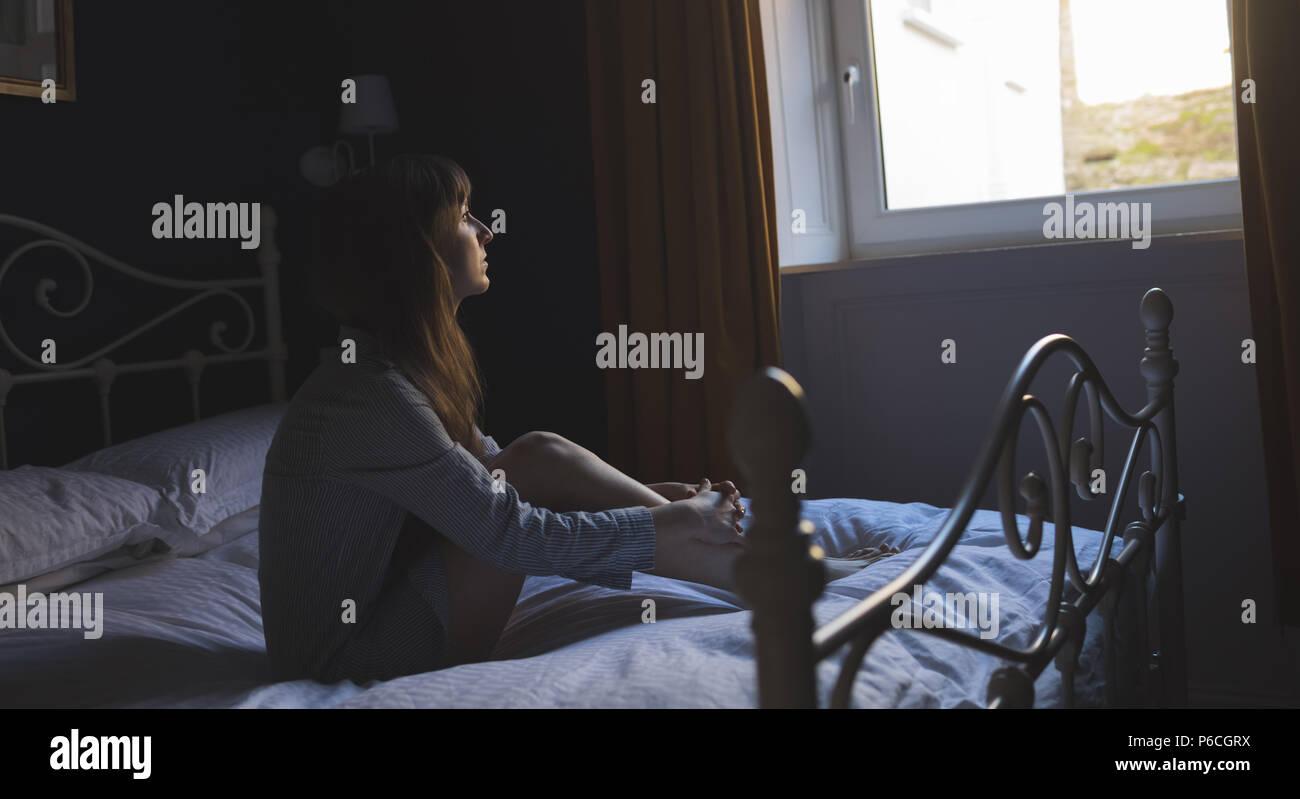 Femme regardant la fenêtre tandis qu'assis sur le lit Banque D'Images