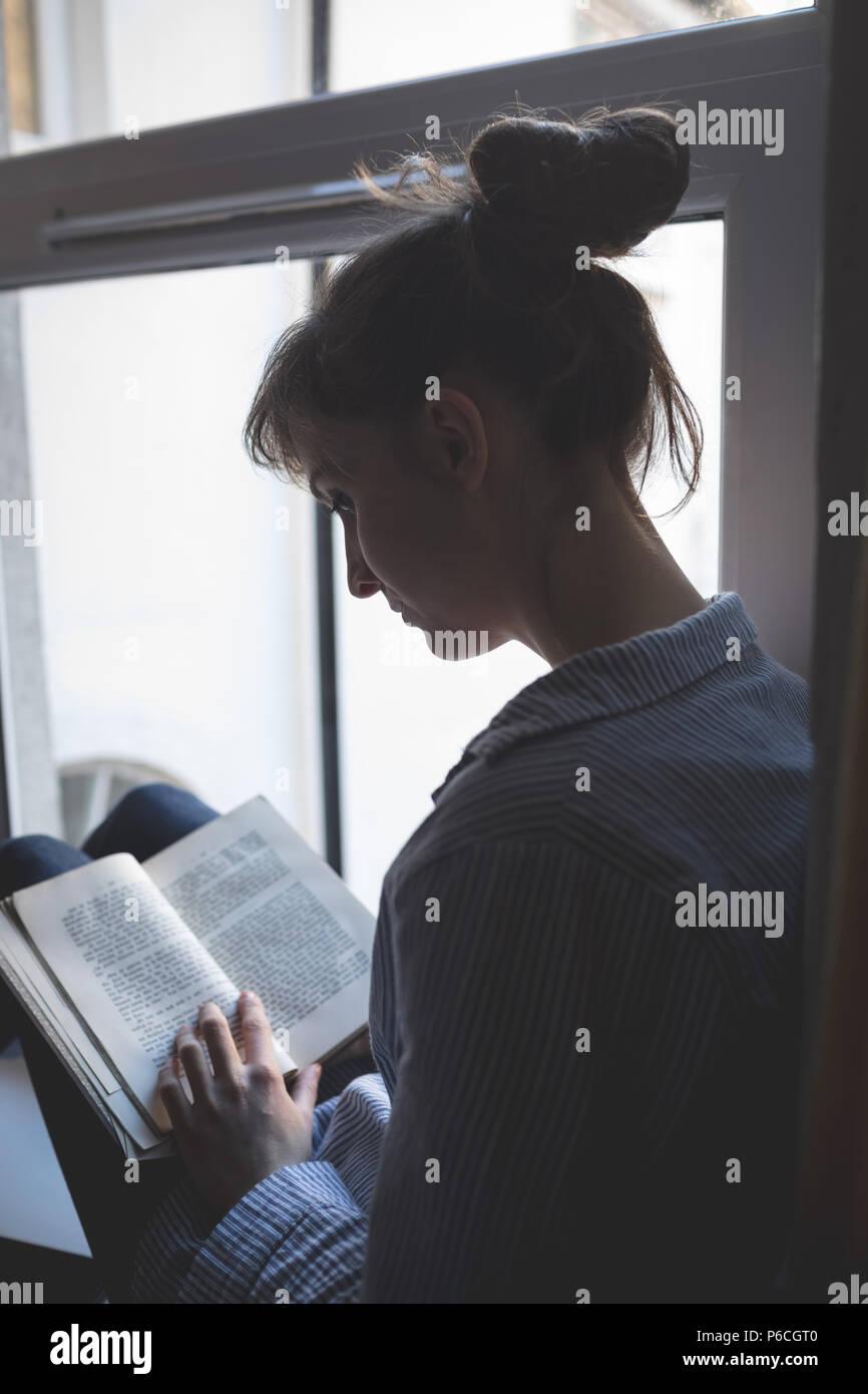 Fenêtre près de Woman Reading book Banque D'Images