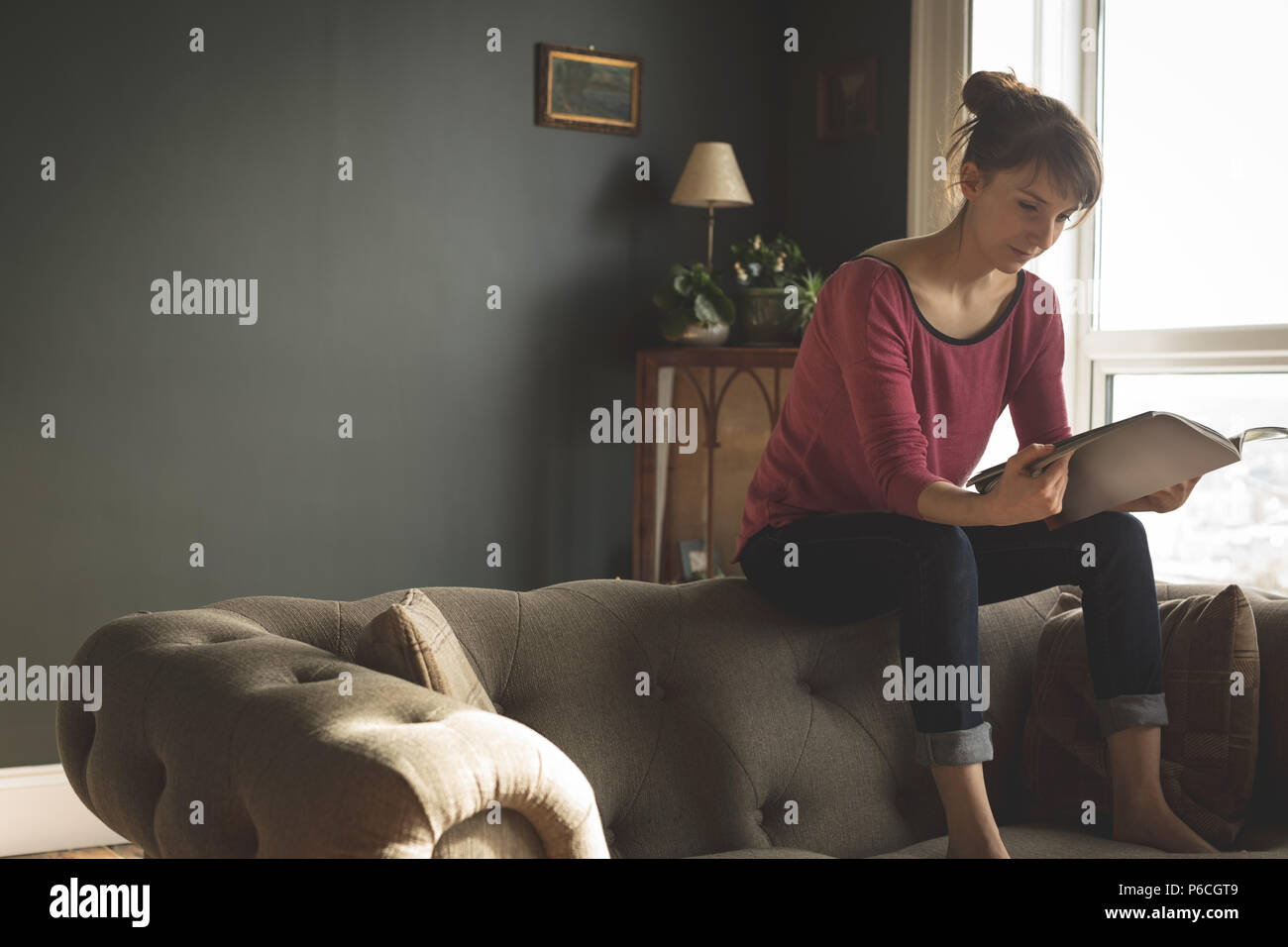 Woman Reading book in living room Banque D'Images