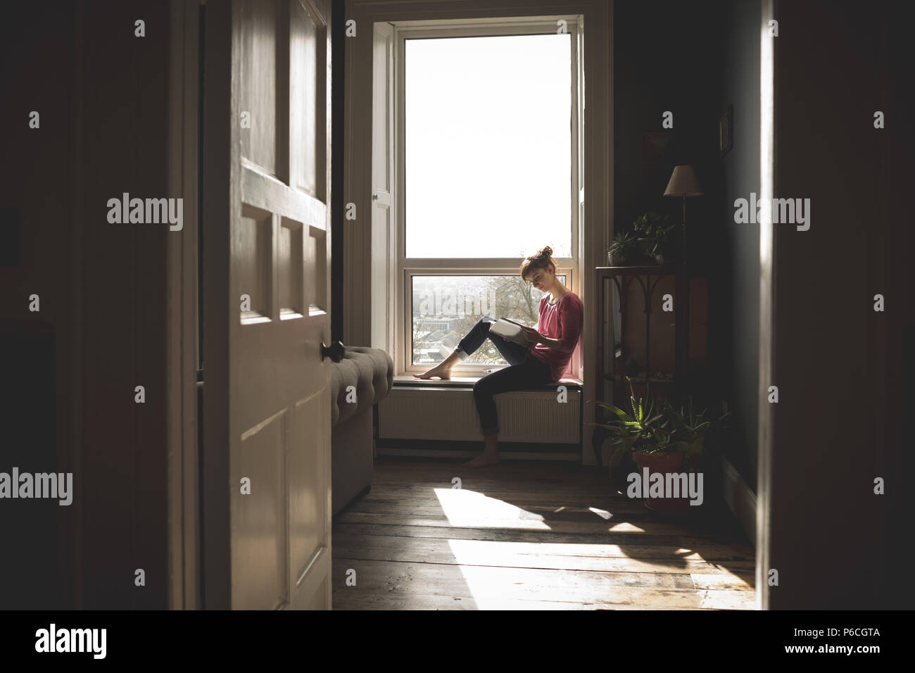 Woman Reading book on window sill Banque D'Images