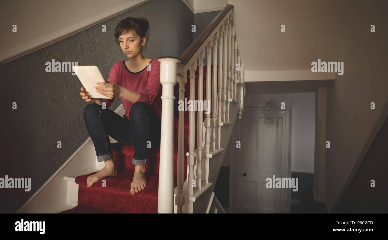 Woman using digital tablet on staircase Banque D'Images