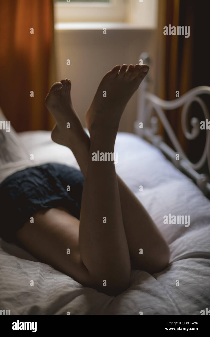 Woman lying on bed at home Banque D'Images