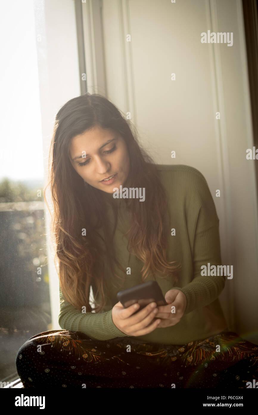 Woman using mobile phone sur à la maison Banque D'Images